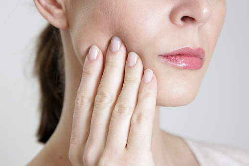 Woman holding her hand to her painful jaw